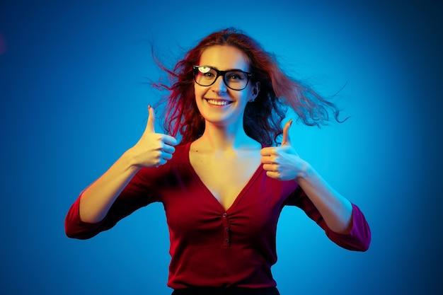 Het portret van de kaukasische die vrouw op blauwe studioachtergrond in neonlicht wordt geïsoleerd. mooi vrouwelijk model met rood haar in casual stijl. concept van menselijke emoties, gezichtsuitdrukking, verkoop, advertentie. duimen omhoog.