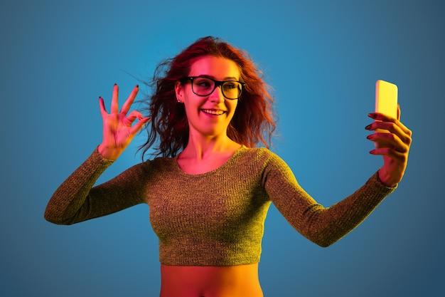 Het portret van de kaukasische die vrouw op blauwe studioachtergrond in neonlicht wordt geïsoleerd.