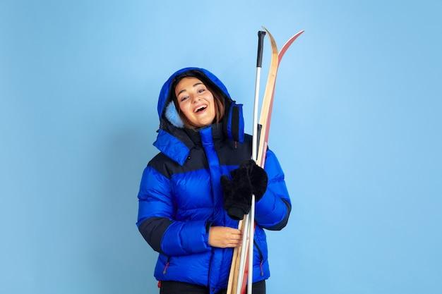 Het portret van de kaukasische die vrouw op blauwe studioachtergrond, winterthema wordt geïsoleerd