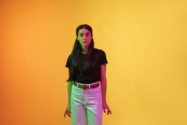 Het portret van de kaukasische jonge vrouw dat op studioachtergrond wordt geïsoleerd in neonlicht.