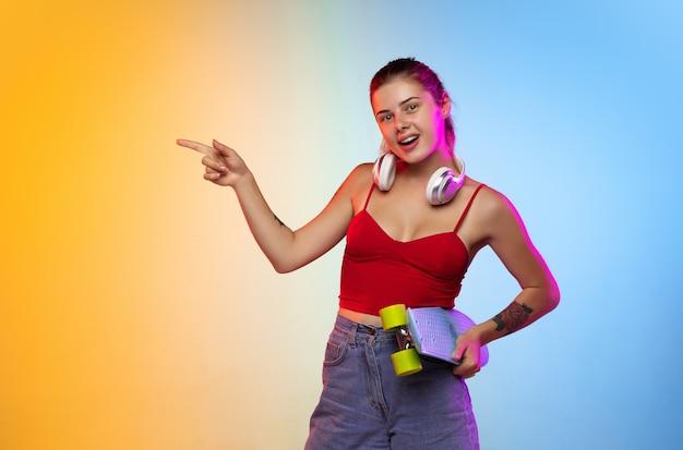Het portret van de kaukasische jonge vrouw op de achtergrond van de gradiëntstudio in neon. mooi vrouwelijk model in casual stijl.