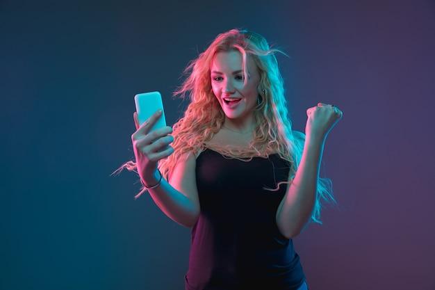 Het portret van de kaukasische jonge vrouw op gradiëntachtergrond in neonlicht. mooi vrouwelijk model met een ongewone uitstraling. concept van menselijke emoties, gezichtsuitdrukking, verkoop, advertentie. selfie maken, wedden, aankopen doen.