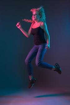 Het portret van de kaukasische jonge vrouw op gradiëntachtergrond in neonlicht. mooi vrouwelijk model met een ongewone uitstraling. concept van menselijke emoties, gezichtsuitdrukking, verkoop, advertentie. springen, glimlachend.