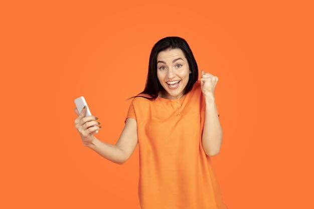 Het portret van de kaukasische jonge vrouw op oranje achtergrond