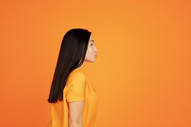 Het portret van de kaukasische jonge vrouw op oranje studio