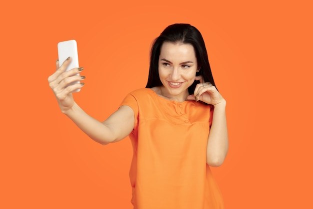 Het portret van de kaukasische jonge vrouw op oranje studioachtergrond. mooi vrouwelijk donkerbruin model in overhemd. concept van menselijke emoties, gezichtsuitdrukking, verkoop, advertentie. copyspace. selfie maken, weddenschap winnen.