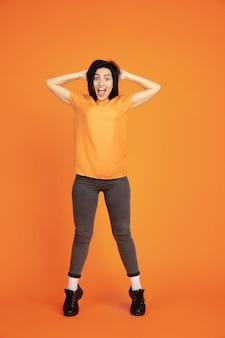 Het portret van de kaukasische jonge vrouw op oranje studioachtergrond. mooi vrouwelijk donkerbruin model in overhemd. concept van menselijke emoties, gezichtsuitdrukking, verkoop, advertentie. copyspace. winnende, gekke blij.