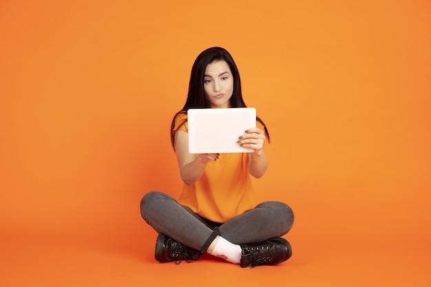 Het portret van de kaukasische jonge vrouw op oranje studioachtergrond.