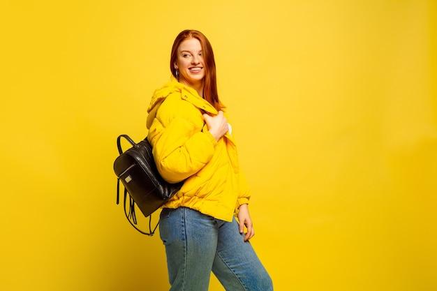 Het portret van de kaukasische vrouw dat op gele studioachtergrond wordt geïsoleerd, volgeling wordt zoals