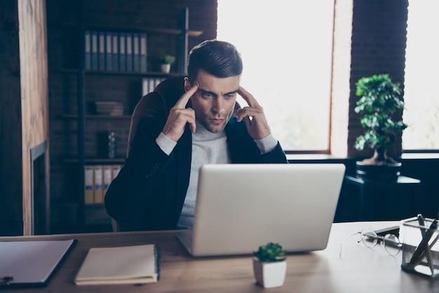 Het portret van de kerel zit werkplek computer kijkt