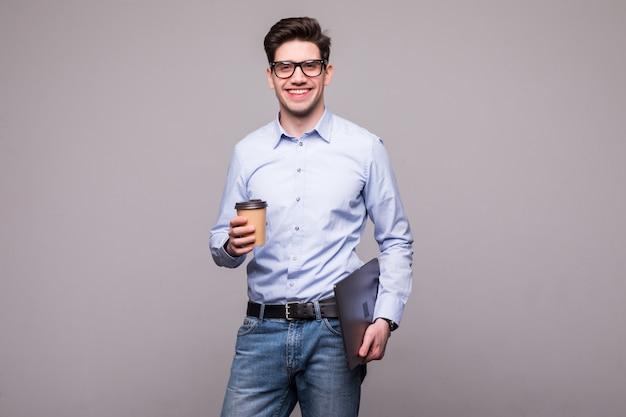 Het portret van de knappe jonge mens kleedde zich in de meeneemkoffie en laptop van de overhemdsholding en weg kijkend over witte ruimte