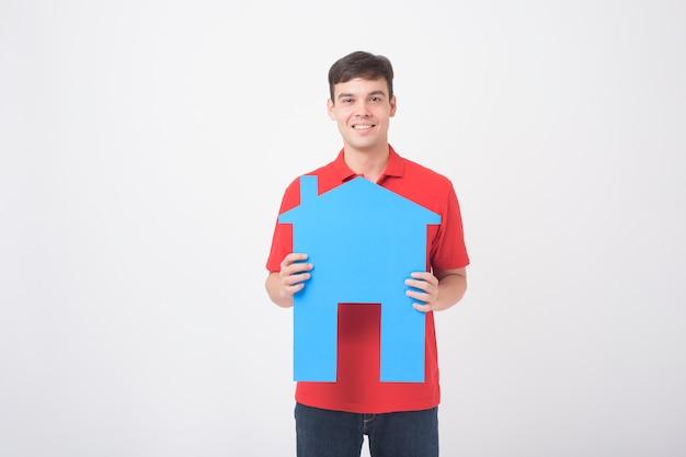 Het portret van de knappe mens houdt document huis op witte achtergrond