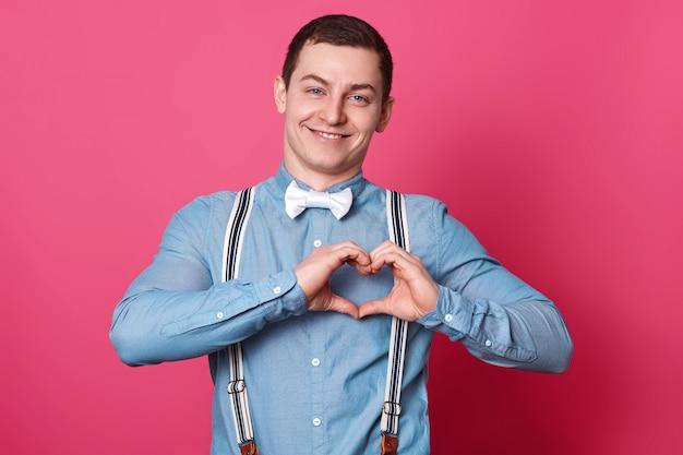 Het portret van de knappe romantische glimlachende jonge mens brengt zijn handen samen makend hartend teken op borst, tevreden en opgetogen blikken. mensen, jeugd en emoties concept.