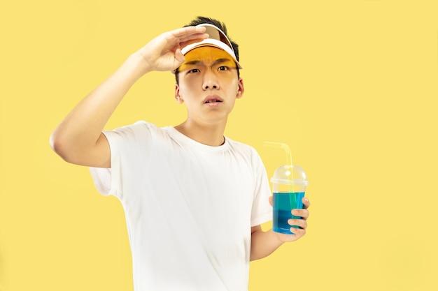 Het portret van de koreaanse jongeman. mannelijk model in wit overhemd en gele pet. cocktail drinken. concept van menselijke emoties, uitdrukking, zomer, vakantie, weekend.