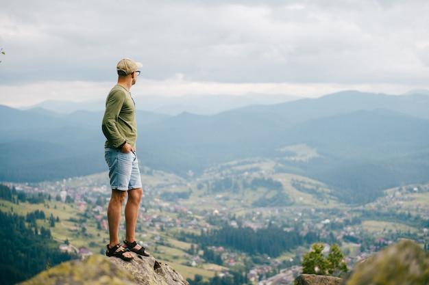 Het portret van de levensstijlzomer van de mens die zich bovenop mountaing met mooi landschap vooraan bevinden. mannelijke reiziger die aard van mening van hoogste piek genieten bij heuvel.