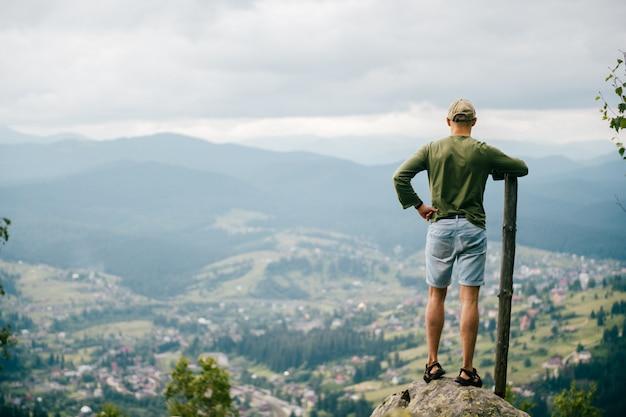 Het portret van de levensstijlzomer van erachter van de mens met houten stok die zich bovenop mountaing met mooi landschap vooraan bevinden. mannelijke reiziger die aard van mening van hoogste piek genieten bij heuvel.