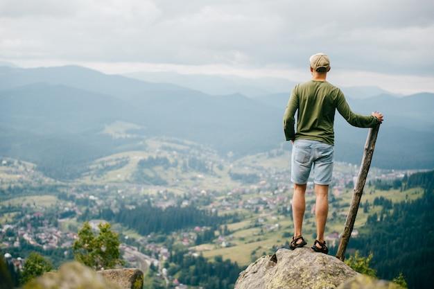Het portret van de levensstijlzomer van erachter van de succesvolle mens met houten stok die zich bovenop mountaing met mooi landschap vooraan bevinden.