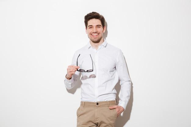 Het portret van de manier jonge mens kleedde zich in overhemd glimlachend en stellend op camera die zwarte zonnebril, over witte ruimte met schaduw houden