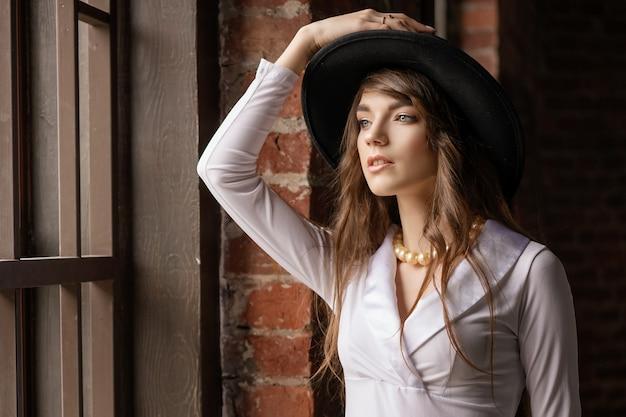 Het portret van de manier van jonge mooie zekere vrouw die hoed draagt, die binnen bij het venster stelt
