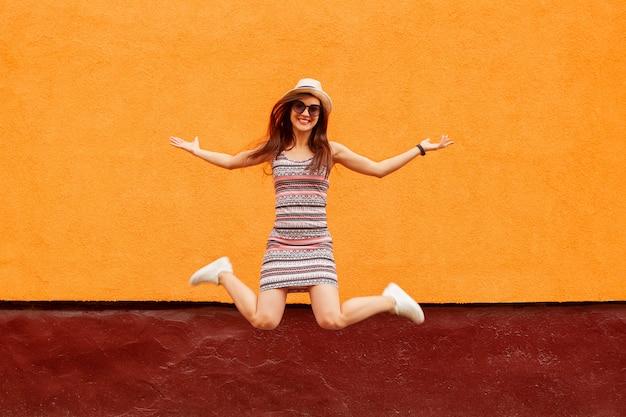 Het portret van de manier van mooie glimlachende vrouw in zonnebril en hoeden het springen