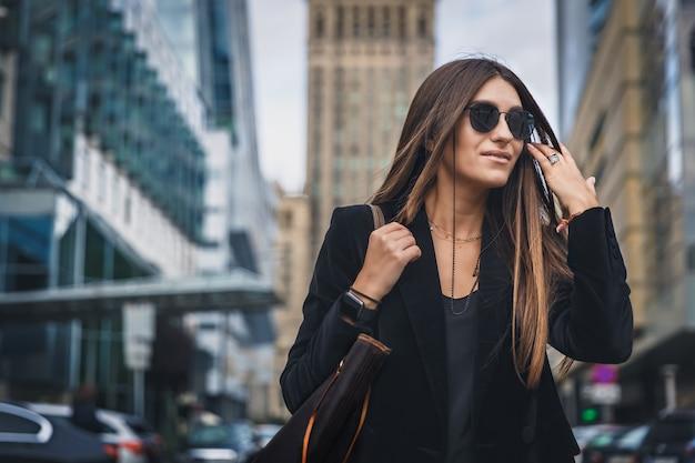 Het portret van de maniervrouw van het jonge vrij trendy meisje stellen bij de stad in europa.