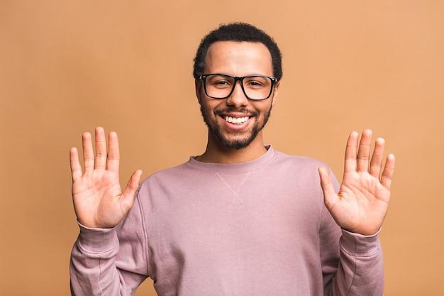 Het portret van de mannelijke hand dient stopbord in, waarschuwt en voorkomt u van iets slechts, kijkend naar de camera met bezorgde uitdrukking