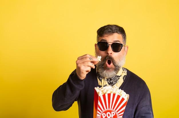 Het portret van de mens met witte baard en zonnebril die popcorn eten verbaasde het letten op televisie op gele achtergrond.