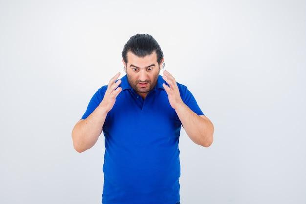 Het portret van de mens van middelbare leeftijd die overhandigt overhandigt borst in blauw t-shirt en verbaasd vooraanzicht kijkt