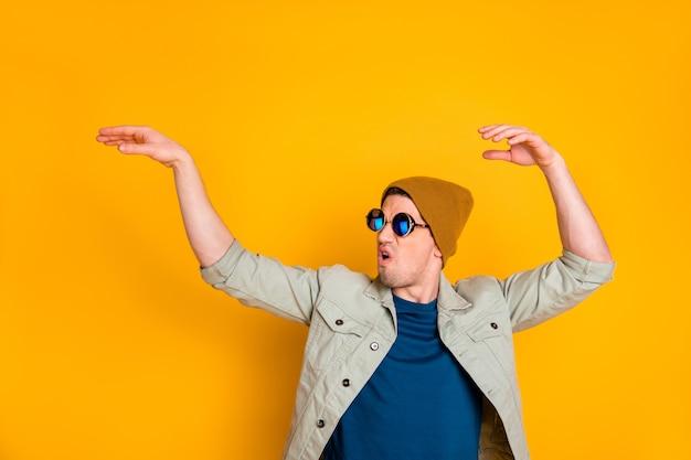Het portret van de moderne dansdiscovloer van de man steekt de hand op en kijkt copyspace geïsoleerd over een levendige kleurenachtergrond