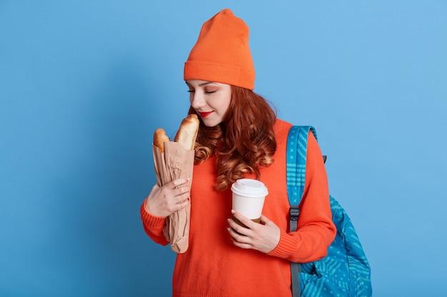 Het portret van de mooie jonge document zak van de vrouwenholding met brood en haalt koffie weg