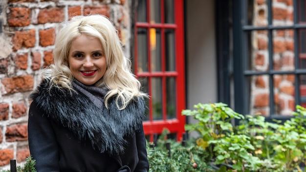 Het portret van de nieuwe, glimlachende, blonde vrouw op het defocused rode baksteengebouw