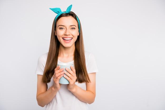 Het portret van de positieve vrolijke funky mok van de meisjesgreep met hete cafeïnedrank heeft pret met vrienden in geïsoleerde koffiekleding modieuze outfit