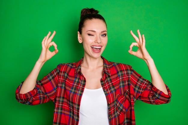 Het portret van de positieve, vrolijke meisjespromotor stelt voor om de perfecte advertenties te selecteren, de promotie te laten zien oke teken knipoogje, het dragen van een goed uitziende kleding geïsoleerd heldere glans kleur achtergrond