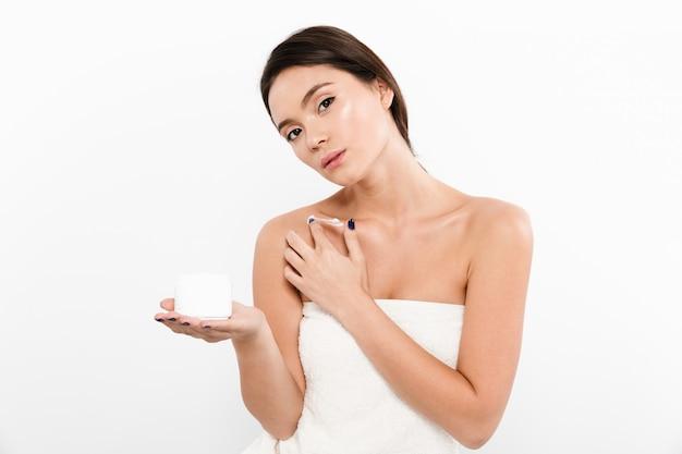 Het portret van de schoonheid van aziatische vrouw die in handdoek bevochtigende room op haar lichaam met in hand kruik toepast, dat over wit wordt geïsoleerd
