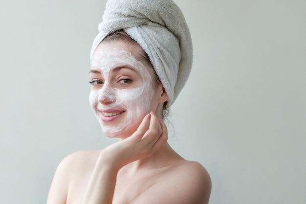 Het portret van de schoonheid van jonge vrouw in handdoek op hoofd die wit voedend masker of room op gezicht toepast dat op witte muur wordt geïsoleerd. huidverzorging reinigende eco organische cosmetische spa ontspannen concept.
