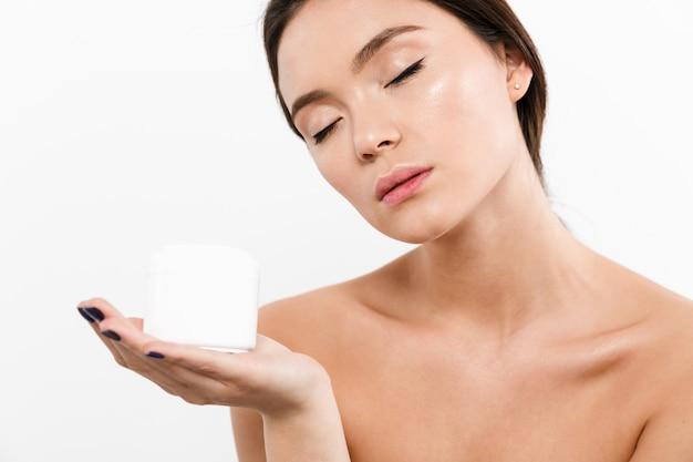 Het portret van de schoonheid van sensuele aziatische vrouw die met gesloten ogen en zwarte pijlen gezichtscrème op haar palm houdt, dat over wit wordt geïsoleerd