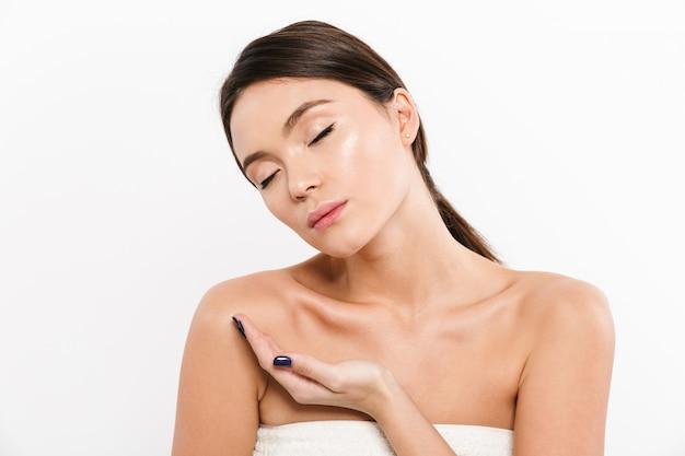 Het portret van de schoonheid van zachte aziatische vrouw die met gesloten ogen reclameproduct op haar palm houdt, dat over wit wordt geïsoleerd
