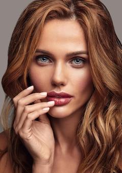 Het portret van de schoonheidsmanier van jong blond vrouwenmodel met natuurlijke make-up en het perfecte huid stellen. haar mond aanraken