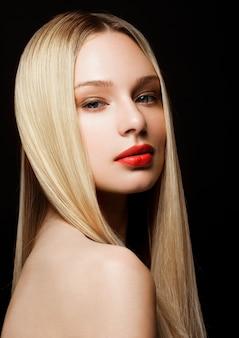 Het portret van de schoonheidsmannequin met glanzend blondekapsel met rode lippen op zwarte achtergrond
