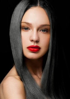 Het portret van de schoonheidsmannequin met glanzend donkerbruin kapsel met rode lippen op zwarte achtergrond