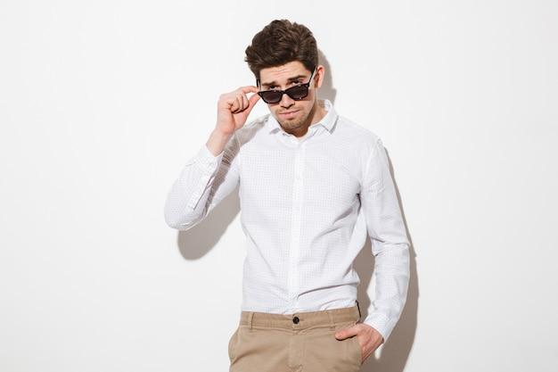 Het portret van de seksuele mannelijke mens kleedde zich in overhemd kijkend op camera van onder zwarte zonnebril, over witte ruimte met schaduw