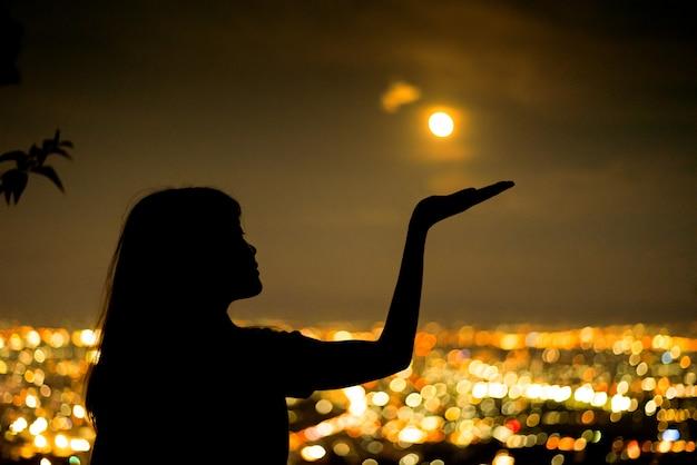 Het portret van de silhouetvrouw met volle maan op lichte bokehachtergrond van de stadsnacht