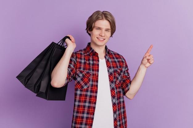 Het portret van de vrolijke man van de adviseur, de lege ruimte met de vinger, draagt winkeltassen op een violette achtergrond
