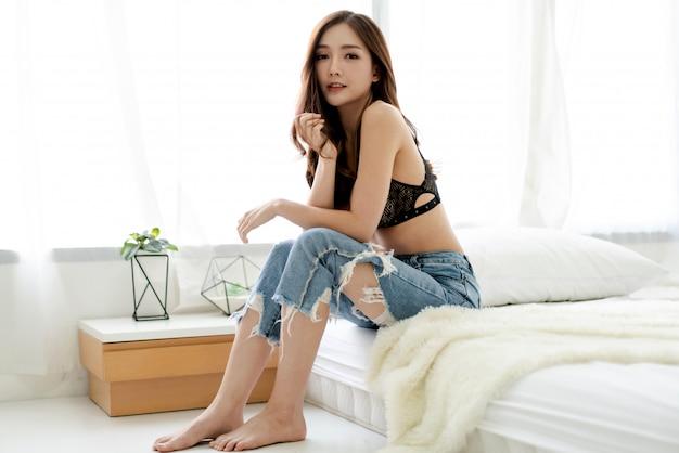 Het portret van de vrouw van azië geniet van en ontspant op het bed