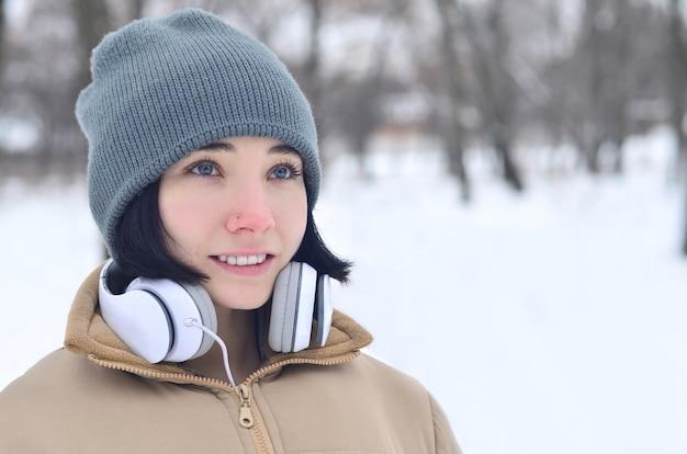 Het portret van de winter van jong meisje met hoofdtelefoons
