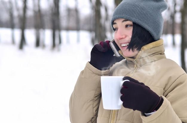 Het portret van de winter van jong meisje met smartphone en koffiekop