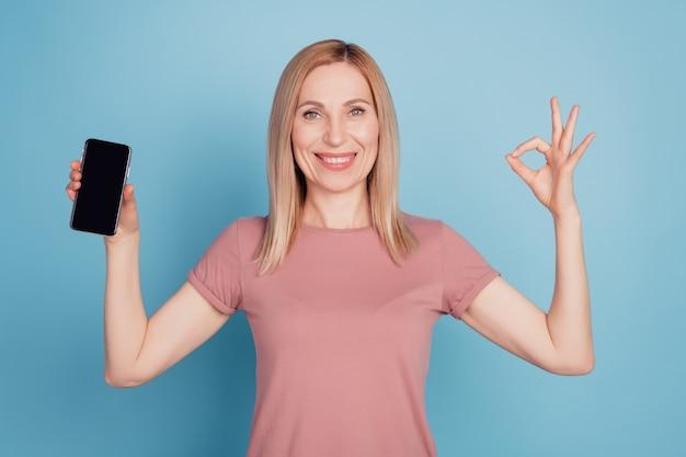 Het portret van een aardige, aantrekkelijke charmante, vrolijke dame toont een goed teken, een perfecte advertentie-mobiel geïsoleerd op een blauwe achtergrond