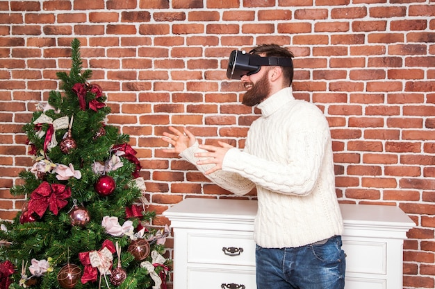 Het portret van een bebaarde man met een virtual reality-bril in de buurt van de nieuwjaarsboom