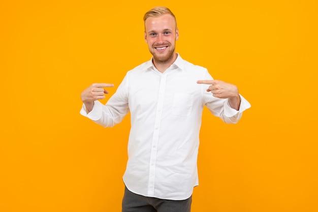 Het portret van een blonde jonge mens in een wit overhemd toont zich met een lay-out op geel met exemplaarruimte