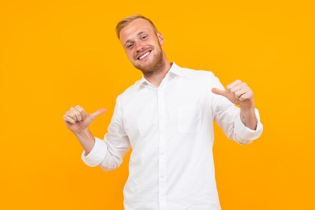 Het portret van een blonde jonge mens in een wit overhemd toont zich met een lay-out op geel